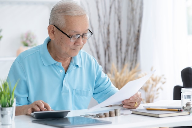 재정, 저축, 연금 보험 및 사람들 개념-계산기와 집에서 돈을 계산하는 청구서 수석 남자. 집에서 세금을 계산하는 수석 남자
