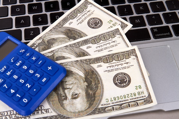 ノートパソコン、電卓、机の上の現金の財務会計の概念