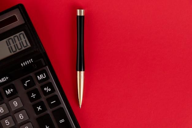 Финансовая деятельность, бухгалтерский учет, расчет налогов или сбережений и инвестиций, черный калькулятор с ручкой на сплошном красном фоне с местом для копирования.