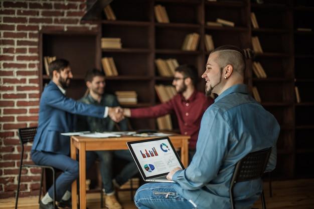 재무 관리자는 현대 사무실에서 핸드 쉐이킹하는 비즈니스 파트너의 배경에 재무 그래프로 작업합니다.