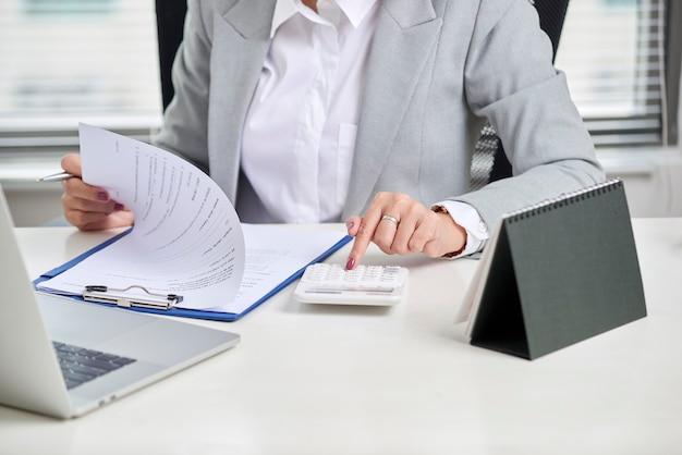 電卓を使用するファイナンシャルアドバイザーは、机の上で財務諸表を確認します。会計の概念。