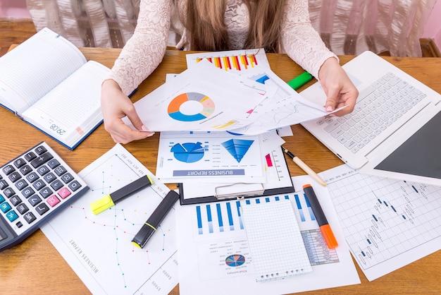 Финансовый аналитик, сравнивая бизнес-графики, рабочее место, офис