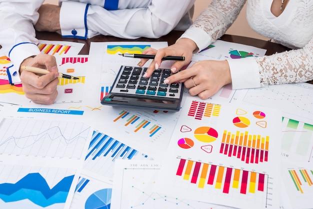 電卓でビジネスレポートを数える金融アナリストチーム