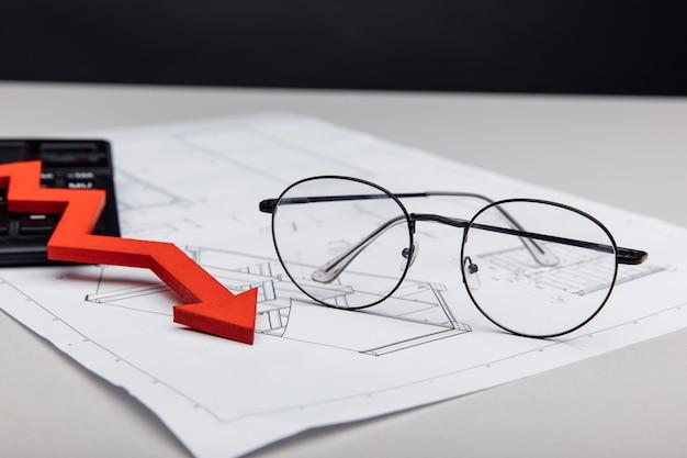 금융 및 투자 개념 안경 및 건축 프로젝트 근접 촬영에 아래로 화살표