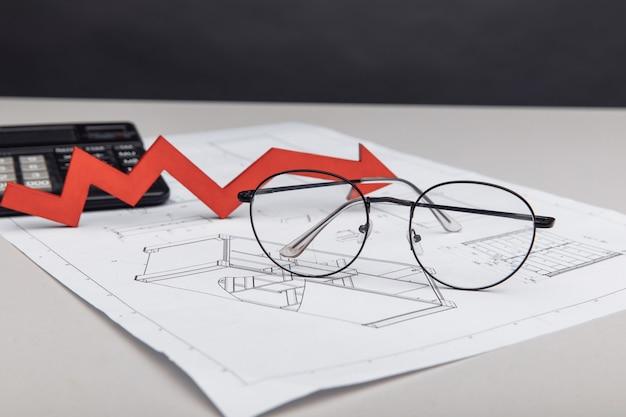 금융 및 거래 개념입니다. 건축 프로젝트에 계산기, 안경 및 화살표.
