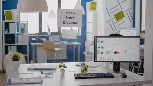 誰もいない空のオフィスでの金融ビジネスのグラフは、壁に社会的距離の兆候を保ちます。コロナウイルス感染症19経済危機時のプラスチックセパレーター