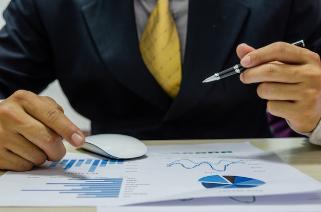 金融ビジネスマンは、収入-費用を分析およびチェックするグラフを文書化します。