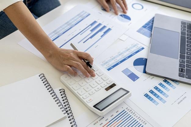 흰색 계산기를 누르는 금융 비즈니스 여성, 그녀는 계산기를 사용하여 부서 직원이 회의 문서로 만드는 회사 재무 문서의 숫자를 계산합니다.