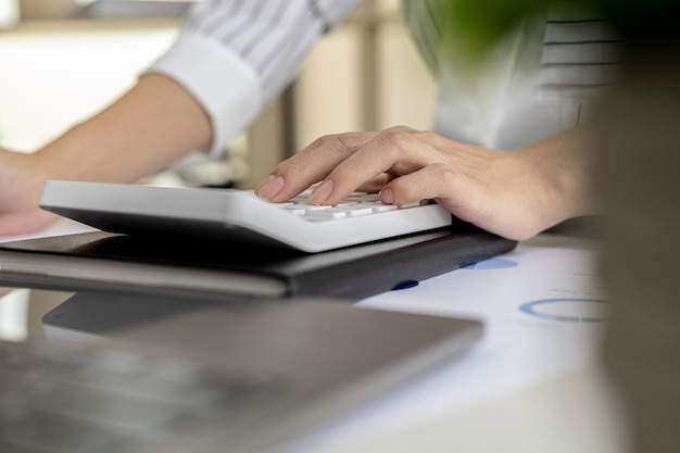 Financial business woman pressing a white calculator, she uses a calculator to calculate the numbers in the company's financial documents that employees in the department create as meeting documents.