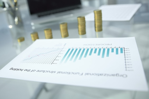 재무 차트 및 사무실 책상에 동전의 스택입니다. 복사 공간이 있는 사진
