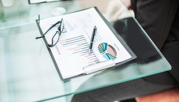 ビジネスマンの職場の財務チャート、メガネ、ペン。写真にはテキスト用の空きスペースがあります