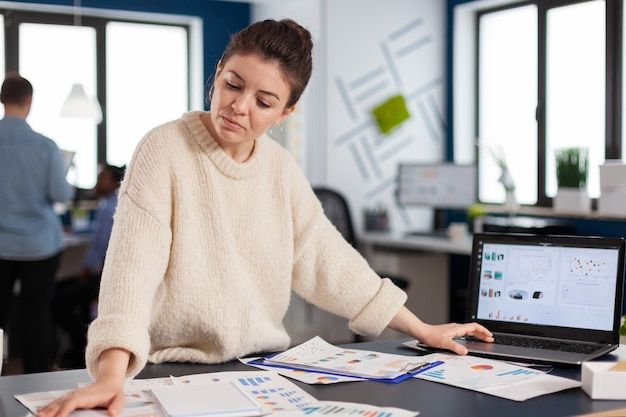 スタートアップ企業で、デスクに立っている事業主によって分析された財務チャート。成功した企業のプロの起業家オンラインインターネット統計、エグゼクティブ起業家、マネージャーリーダースタン