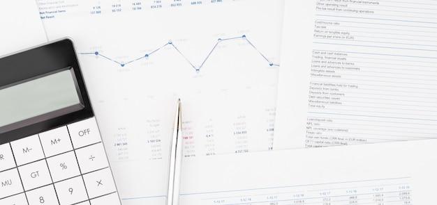 Финансовые графики и калькулятор на столе бухгалтера. расчет прибыли, налогов и выплаты заработной платы сотрудникам.