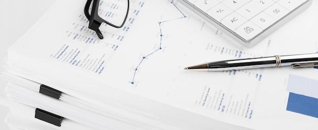 회계사의 책상에 재무 차트와 계산기. 이익, 세금 계산 및 직원 급여 지급.