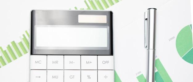 회계사의 책상에 있는 재무 차트와 계산기. 이익, 세금 및 직원 급여를 계산합니다.