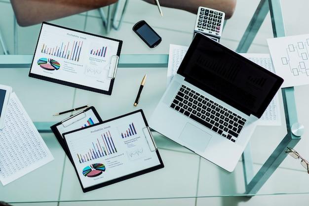 Финансовые диаграммы, маркетинговые диаграммы, ноутбук и калькулятор на рабочем месте бизнесмена