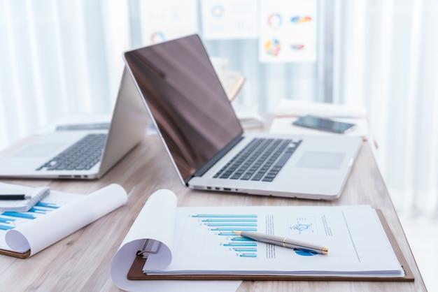 Финансовые диаграммы на столе с ноутбуком