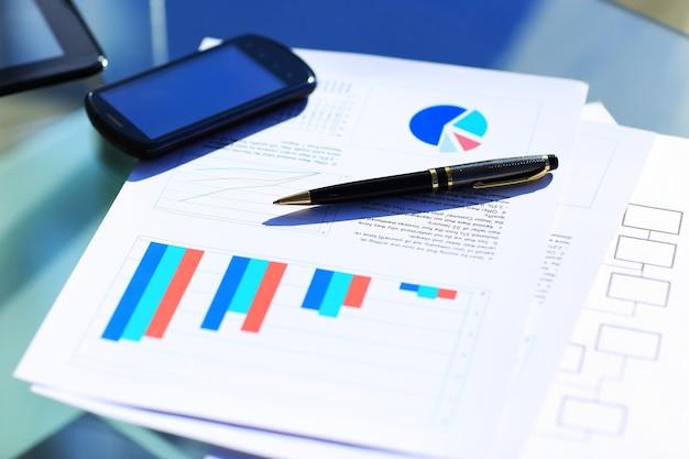 Финансовые графики на столе с планшетом и ручкой