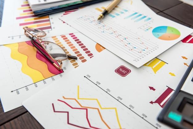 Финансовые диаграммы, работа на бумажной бизнес-диаграмме с ручкой в офисе. график рыночного учета