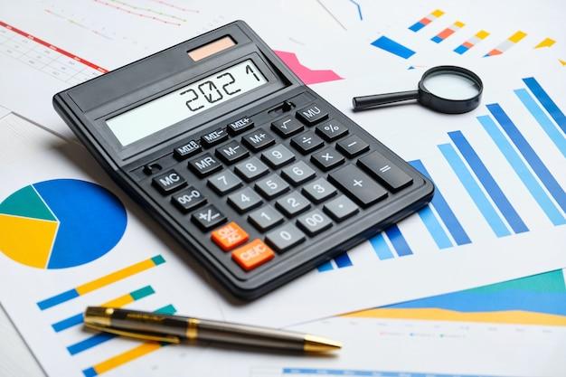 Финансовая концепция 2021 года на калькуляторе и графиках.