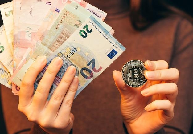 財務コンセプト、オンラインでお金を稼ぐ。手はお金とビットコインのスタックを持っています。閉じる