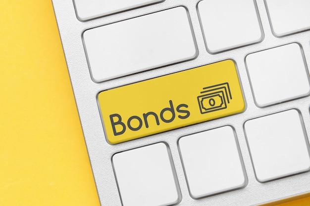 Финансовая концепция с облигациями на кнопке клавиатуры. закройте вверх. Premium Фотографии