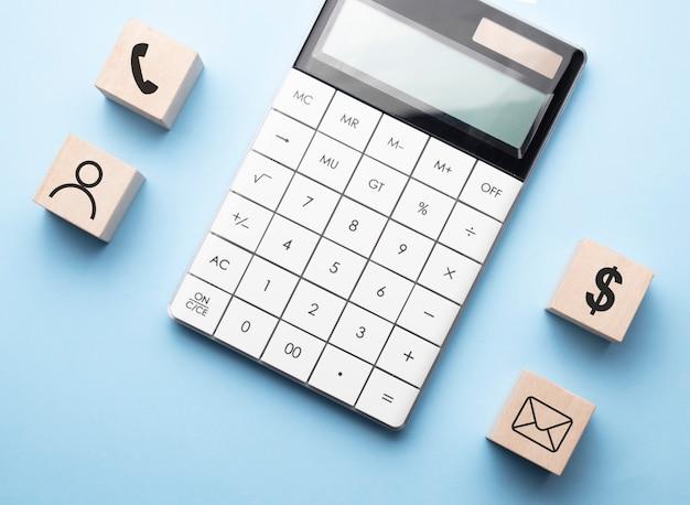 木製の立方体にアイコンを付けた金融コンセプト、青い表面に電卓