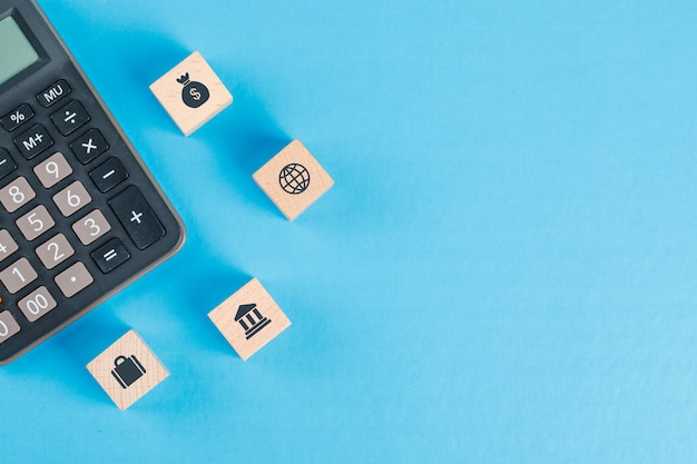 Financial concept with icons on wooden cubes, calculator on blue table flat lay.