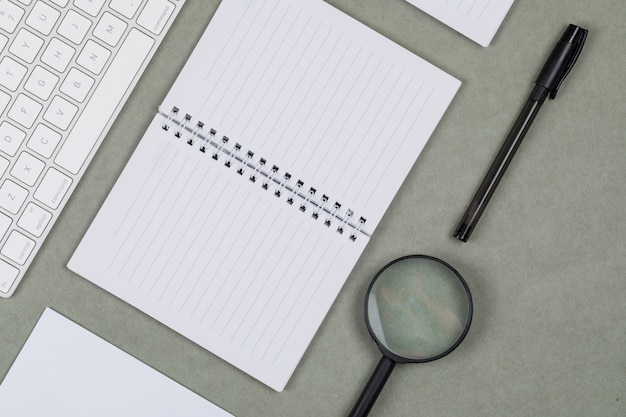 ノートブック、紙、ペン、虫眼鏡、平らな灰色の背景上のキーボードと金融の概念を置きます。