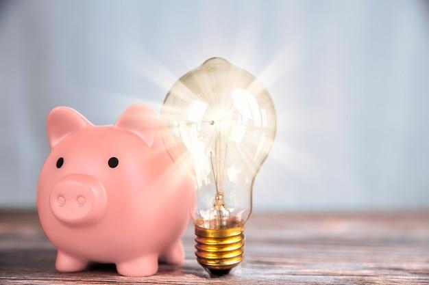 輝く電球と貯金箱を備えた財務コンセプト
