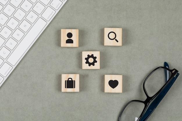 Финансовая концепция с деревянными кубиками, очки, клавиатура на сером фоне плоской планировки.