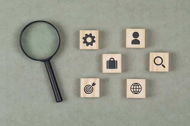 Financial concept with wooden cubes, magnifying glass on grey background flat lay.