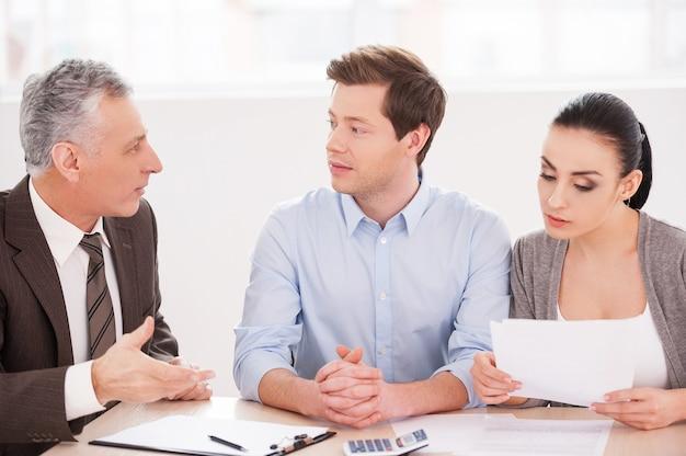 Финансовая консультация. молодая пара сидит за столом, пока старший мужчина в строгой одежде что-то говорит и жестикулирует