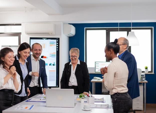 ノートパソコンを見て会議室で大喜びした金融企業チーム