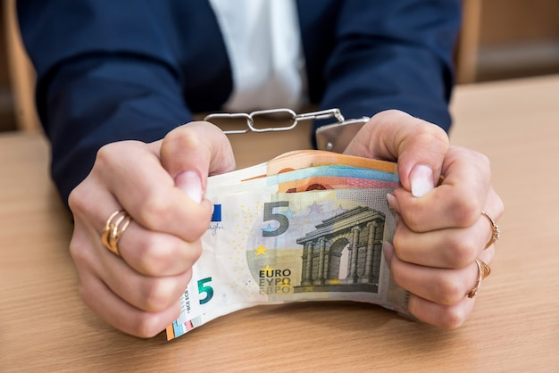 Financial crime concept - female hands with handcuffs and euro bills