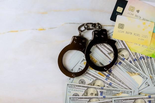 금융 범죄 신용 카드와 달러 지폐 수갑을 훔친 신용 카드 돈과 지문 기록 미국 달러 지폐 돈 현금 부패