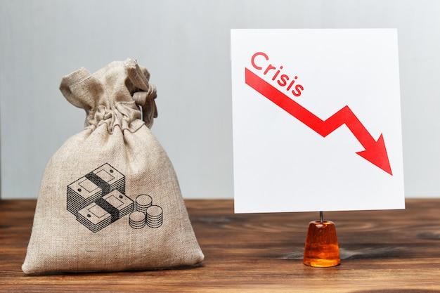 Концепция финансового кризиса. мешок с деньгами рядом с падающим графиком