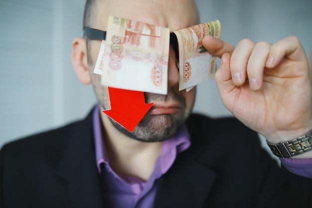 経済危機。コンセプト。手元の金銭法案。国の通貨の下落の矢印記号。ロシアルーブルと米ドルの間の為替レートの変化。