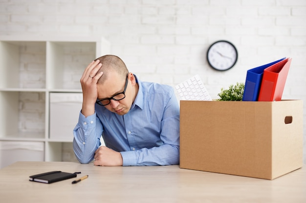 Financial crisis concept - sad businessman sitting in office with moving boxes, covering face with his hand