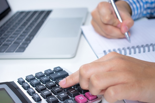 Financial data analysis, hand writing and counting on a white desk. close up.