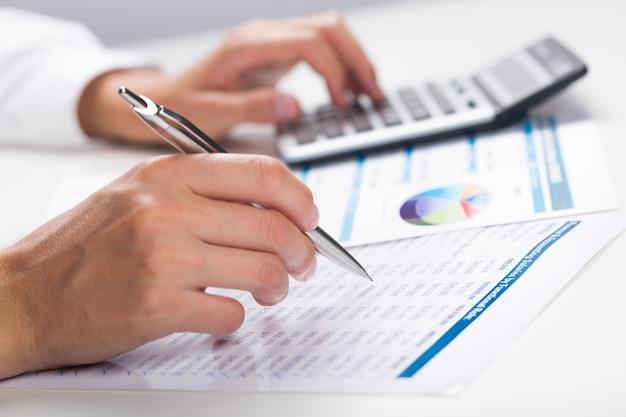 財務データ分析。オフィスで電卓を頼りにビジネスマンの手のクローズアップ写真。