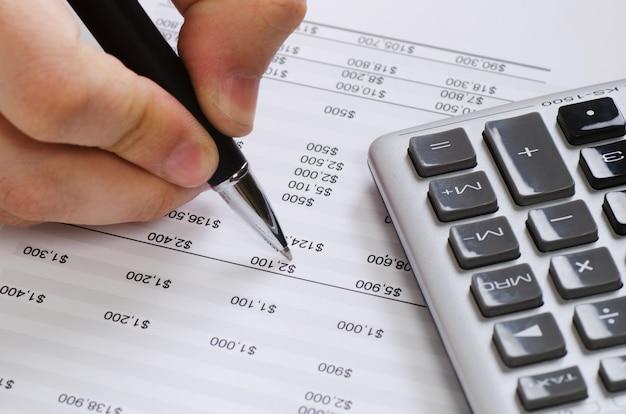 財務データの分析。オフィスで電卓を頼りにビジネスマンの手のクローズアップ写真。