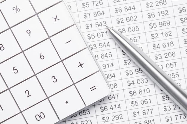 財務データ分析。電卓を頼りに。電卓にペンで手。