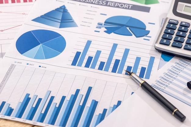 チャートとグラフ用紙上の金融開発計算機とペン。
