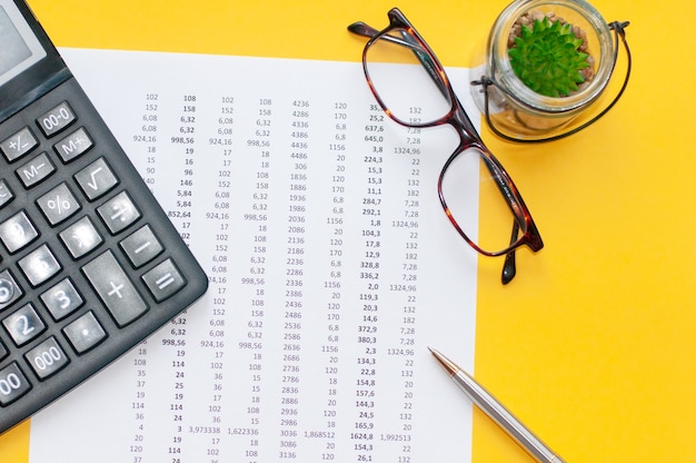 On financial documents with columns of numbers is a black calculator. pen and glasses for vision. business and financial concept