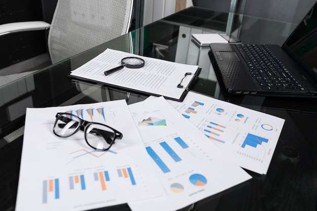 虫眼鏡と保険の財務書類は、オフィスのクローズアップで黒いテーブルにあります。