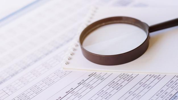 Финансовые документы с увеличительным стеклом и блокнотом над ними