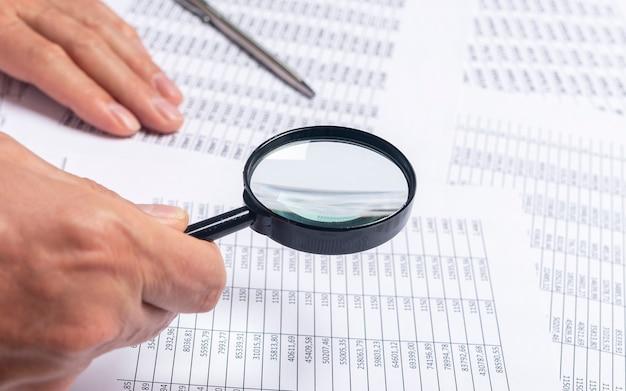 Финансовые документы с увеличительным стеклом над ними в мужских руках