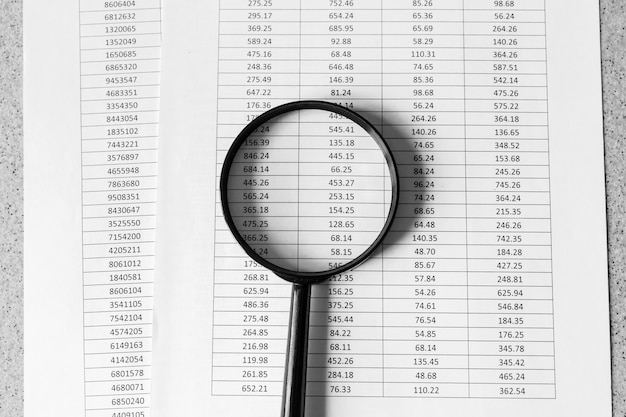 Financial documents with magnifying glass on them