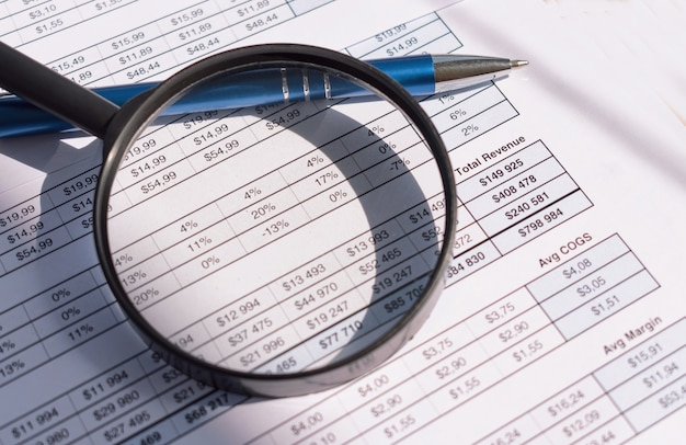 Financial documents with pen and magnifying glass.